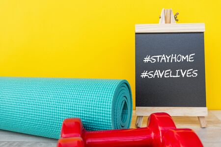 Blackboard with words #stay home #save lives and yoga mat and pink dumbbell -  Corona virus Covid - 19 lock down, restricted movement and workout exercise concept. Imagens - 144566434