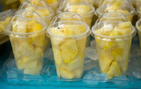 Fresh pineapple pieces salad in plastic transparent cups for sale at farmers market