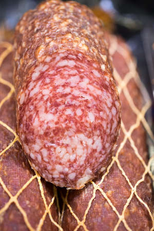 salami sausages showed at refrigerated store window