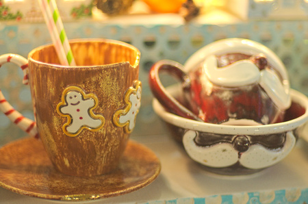 Brown clay cup with gingerbread ornament in front of dark brown cups with mustache