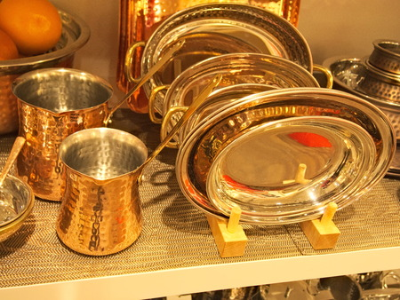 Various orange cooper kitchen cookware, coffeepots, coffee makers jars and plates.
