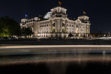 Reichstag building, seat of the German parliament, at night - light trails by a ship passing the scene Editorial