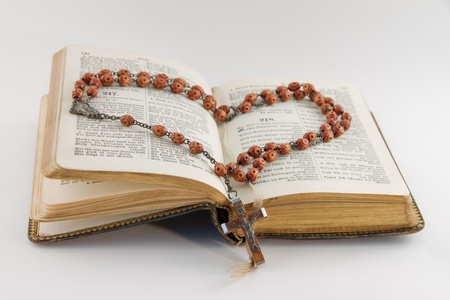 pew: Old hymnal and a rosary