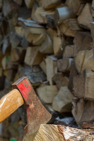Axe in front of a pile of wood photo
