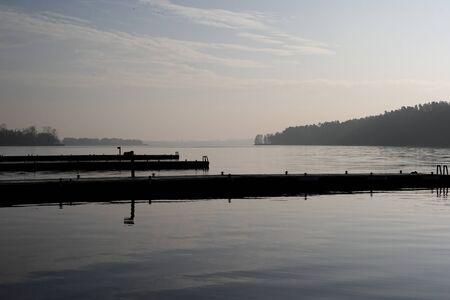 Calm lake with balks on a foggy winter day Standard-Bild