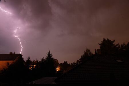A lightning going from cloud to ground during a summer thunderstorm at night Standard-Bild