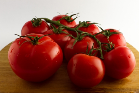 Fresh tomatoes placed on a wooden plate and isolated from a white background