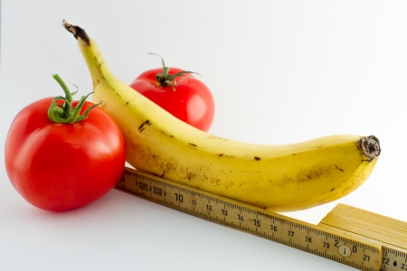 Measuring the size of a penis symbolized by fruits, vegetables and a folding rule
