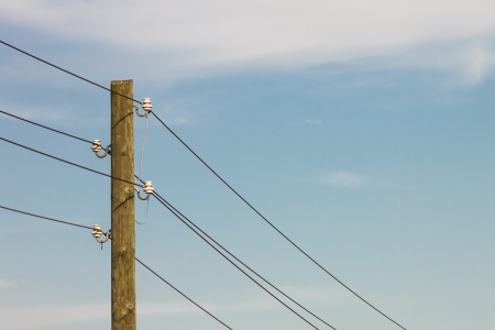 Close-up picture of an old wooden power pole with wires