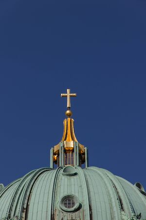 Cross made of gold on top of Berlin Cathedral photo