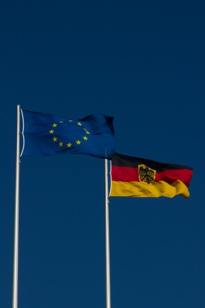 The flags of the European Union and of Germany in front of a deep blue sky blown by the wind