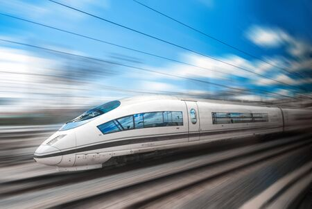 The high speed train rushes through the city by rail