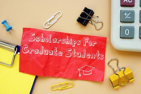 Scholarships For Graduate Students inscription on the piece of paper. Foto de archivo