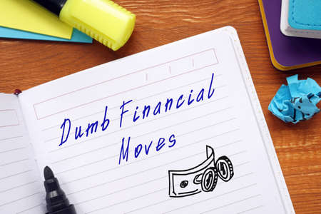 Business concept about Dumb Financial Moves with inscription on the sheet.