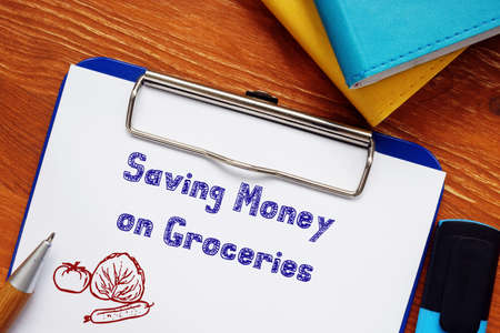Saving Money On Groceries inscription on the sheet. Archivio Fotografico