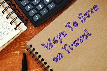 Business concept meaning Ways To Save On Travel with sign on the sheet. Archivio Fotografico