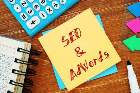 Business concept about SEO & AdWords with sign on the piece of paper.