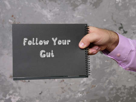 Motivational concept about Follow Your Gut with sign on the page.