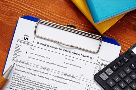 Conceptual photo about Form 921 Consent to Extend the Time to Assess Income Tax with written phrase. Foto de archivo
