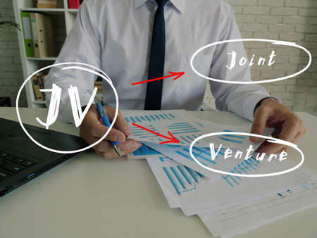Business concept about JV Joint Venture with handwritten phrase. Young Business Man Signing Documents on background.