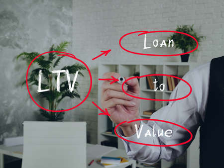 The inscription LTV Loan to Value. Male hand is ready for drawing with black marker on background.