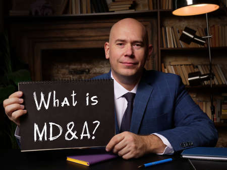 Business concept meaning What is MD&A? Management Discussion and Analysis with phrase on black notepad.