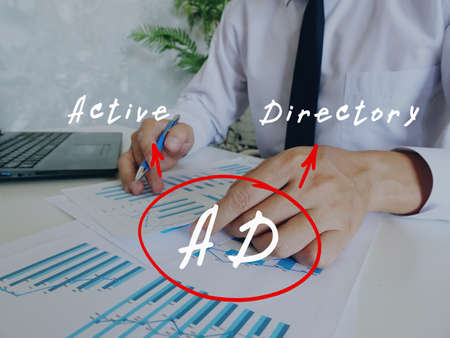 Business concept about AD Active Directory with handwritten text. Busy businessman under stress due to excessive work on background.