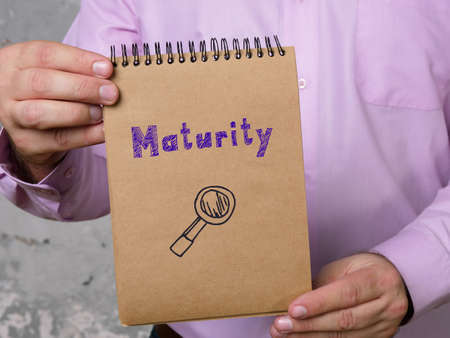 Business concept meaning Maturity with sign on the piece of paper. Foto de archivo