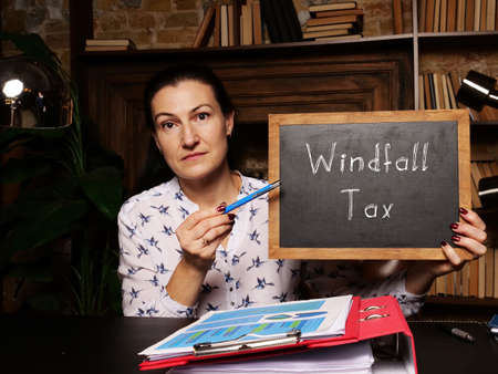 Businesswoman holding a black chalkboard. Business concept about Windfall Tax with phrase on the sheet.