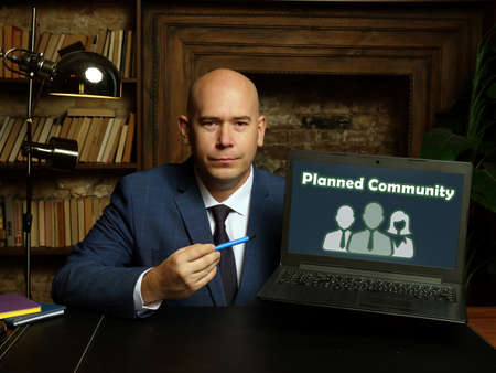 Man wearing blue business suit and showing laptop with written text Planned Community . Blurred background. Horizontal mockup Stock Photo