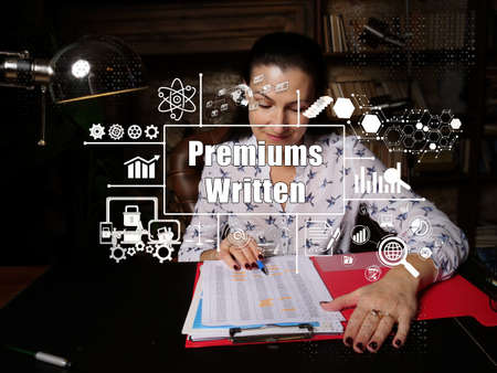 Business concept about Premiums Written with sign. Serious young businesswoman looking report in office on background.