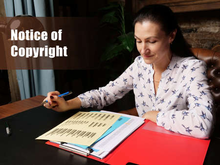 Business concept meaning Notice of Copyright Female office workers with yellow shirt holding and writing documents on office desk