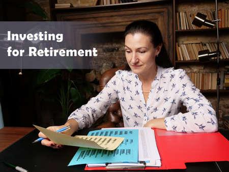 Investing for Retirement phrase. Closeup portrait of unrecognizable successful Businesswoman wearing formal suit reading documents