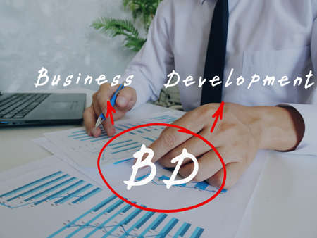Conceptual photo about BD Business Development with written abbreviation. Business Man Checking Documents on background. Stock fotó