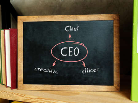 Conceptual photo about CEO Chief executive officer . Blank small chalkboard and different school stationery on wooden table near white wall.