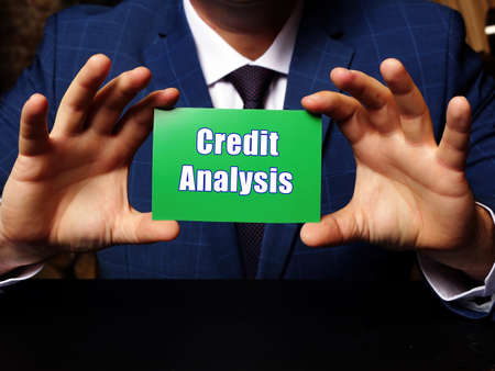 Blank green business card in a hand with phrase Credit Analysis. Horizontal shot. Zdjęcie Seryjne