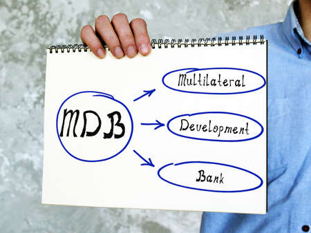 Conceptual photo about MDB Multilateral Development Bank. young adult holding a white notebook