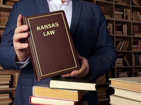 KANSAS LAW book in the hands of a jurist. Kansas residents are subject to Kansas state and US federal laws Stock fotó