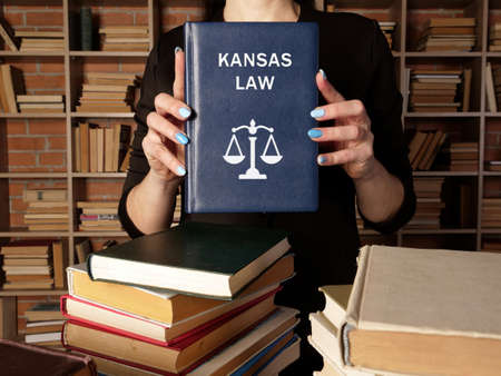 Jurist holds KANSAS LAW book. Kansas residents are subject to Kansas state and US federal laws
