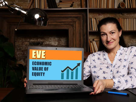 Woman showing laptop computer with EVE ECONOMIC VALUE OF EQUITY icon on screen background, success in business concept