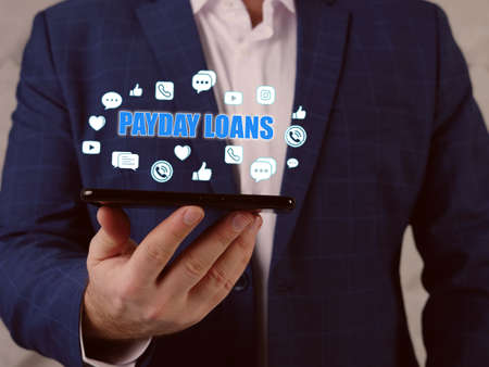 PAYDAY LOANS text in search line. Loan officer looking at smartphone. A payday loan is cash advance offered to help you get to your next paycheck