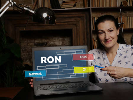 Business woman at work with financial reports RON Run Of Network and a laptop