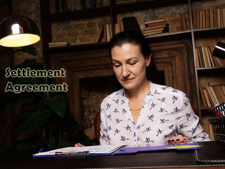 Conceptual photo about Settlement Agreement Businesswoman, executive manager hand filling paper business document Reklamní fotografie