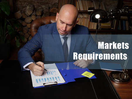 Business concept meaning Markets Requirements Businessman, executive manager hand filling paper business document