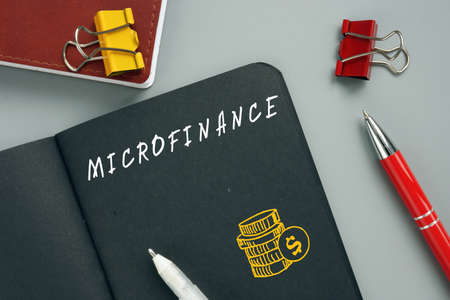 Business concept about MICROFINANCE with inscription on the piece of paper. A banking service provided to unemployed who otherwise would have no other access to financial services