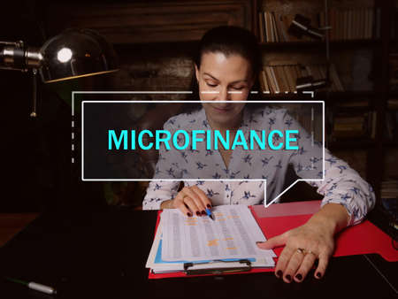 MICROFINANCE phrase on the screen. Marketing expert analyzing market research results. A banking service provided to unemployed who otherwise would have no other access to financial services