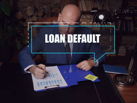 LOAN DEFAULT phrase on the screen. Auditor checking financial report Loan default occurs when a borrower fails to pay back a debt according to the initial arrangement.