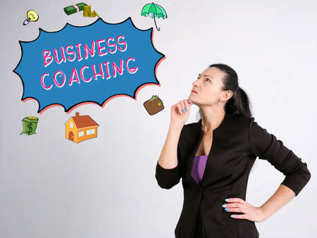 Business concept about BUSINESS COACHING with sign on the gray wall