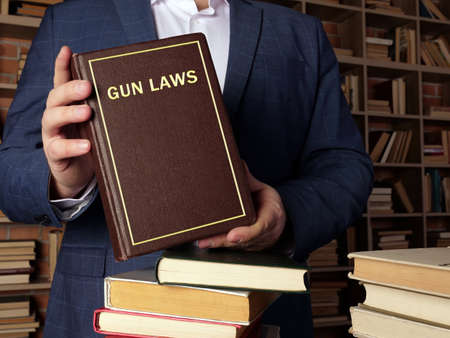 GUN LAWS book in the hands of a jurist. Gun control is one of the most divisive issues in American politics.