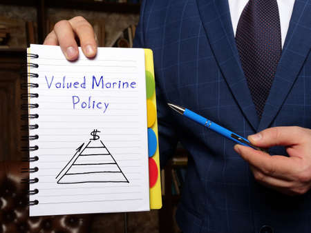 Financial concept about Valued Marine Policy with inscription on the white notepad.
